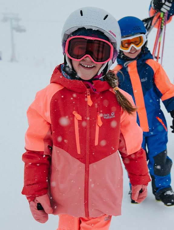 Children dressed up in skiwear and helmets
