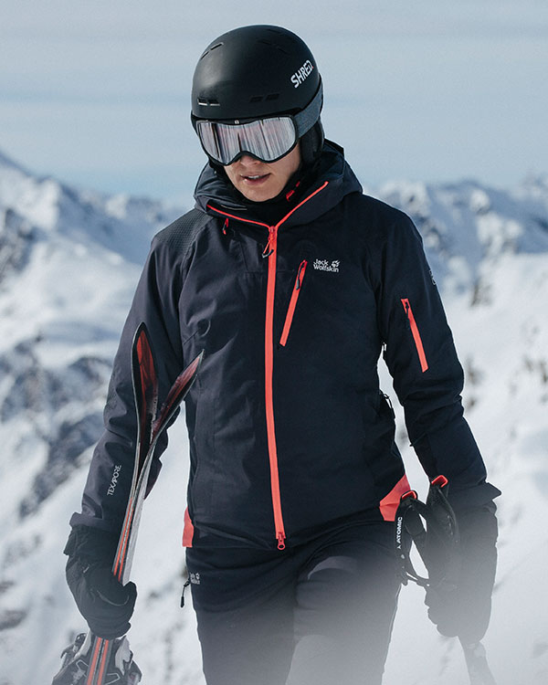 Woman in skiwear and wearing a helmet in front of snow-coveredmountains